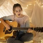 Girl playing a guitar under a tent made of cloth illuminated by a string of ligths