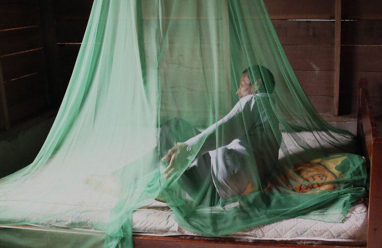 Man sitting under a mosquito repellent net