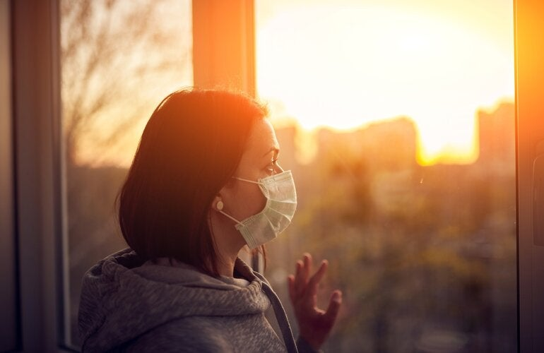 Woman with mask looking out the window at sunset