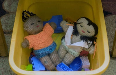 Two dolls in a bucket with other toys