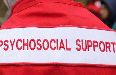 "Photo of the back of a healthcare worker dressed with a red jacket with the sign ""Psychosocial support"" in red typography over white background. Only part of the back is seen, from the top of the shoulders to the mid part of the back"
