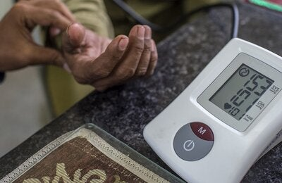 Close up of a glucometer and in the back a hand holding the hand of a patient