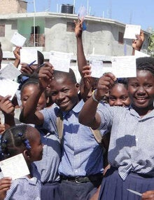 children holding up their vaccination cards