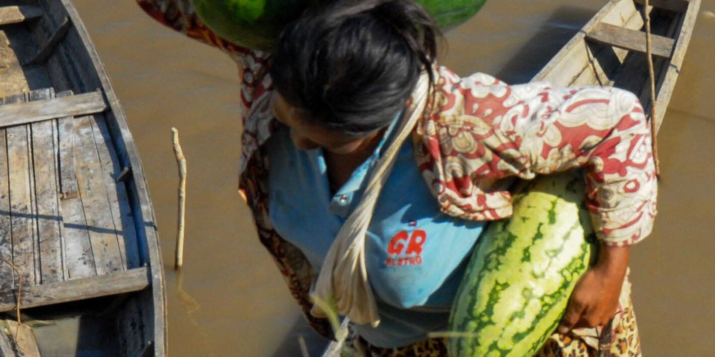 Woman with watermelons and fish in hand