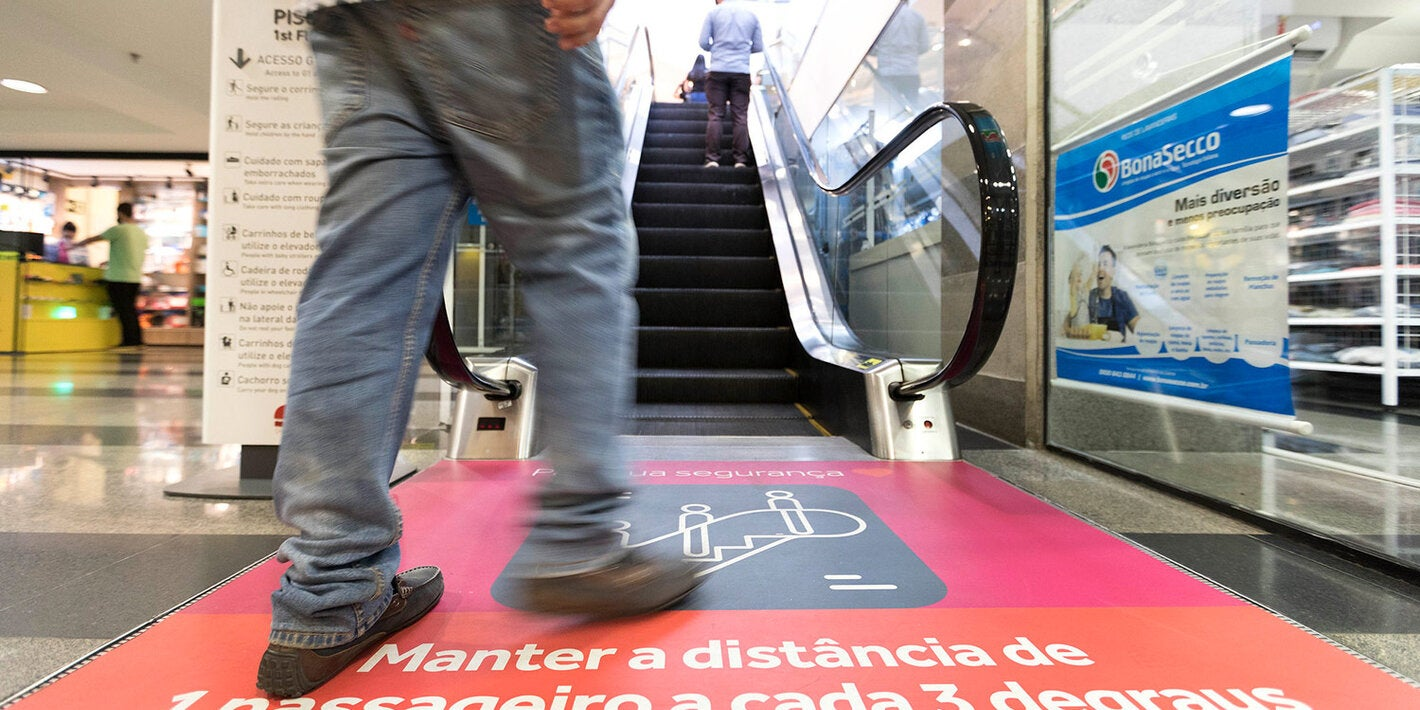 person approaching an escalator with physical distancing recommendations